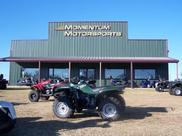 Momentum Motorsports outside storefront with atvs and other inventory displayed out front